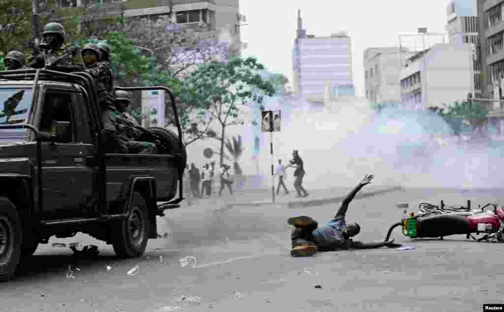A supporter of Kenyan opposition National Super Alliance (NASA) coalition lies on the ground after he was hit by a police truck during a protest along a street in Nairobi.