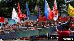 Para demonstran memperlihatkan bagian dari kapal nelayan dengan slogan-slogan anti China dalam unjuk rasa memprotes pertikaian klaim Laut China Selatan, di luar Konsulat China, di Makati City, Metro Manila, Filipina, 12 Juli 2016. REUTERS/Erik