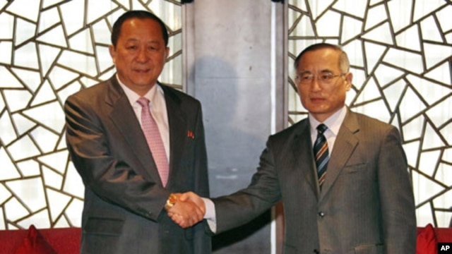 South Korean nuclear envoy Wi Sung-lac (R) shakes hands with his North Korea's counterpart Ri Yong Ho at the private Chang An Club in Beijing, China, September 21, 2011.