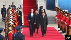 Menlu AS John Kerry (tengah kiri) melewati pesukan kehormatan bersama Wakil Menlu Korea Selatan Lee Kyung-soo (tengah kanan) setibanya di bandara militer di Seongnam, Seoul, Korea Utara (13/2).
