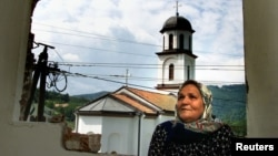 Fata Orlovic, 60, stands in front of the window in her devastated home in the village of Konjevic Polje in eastern Bosnia September 8, 2002