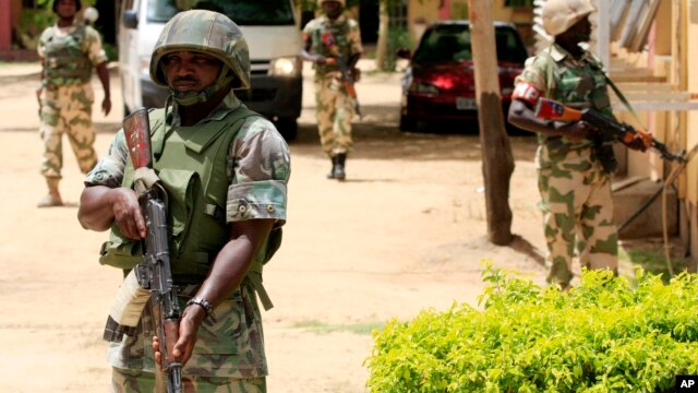 FILE - Nigerian soldiers stand guard at the offices of the state-run Nigerian Television Authority in Maiduguri.