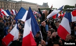 Supporters of Emmanuel Macron celebrate near the Louvre museum after projections were announced in the second round voting in the 2017 French presidential elections, in Paris, France, May 7, 2017.
