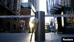 FILE - A bouquet is pictured under police tape near the cordoned-off scene of a hostage taking at Martin Place after it ended early Dec. 16, 2014.