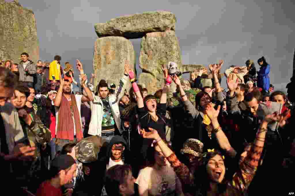 21 tháng 6: Người tham dự reo hò khi ánh mặt trời xuất hiện trong mùa hạ chí tại Stonehenge, Anh quốc. Mùa này tại vùng bắc bán cầu hằng năm thường xảy ra vào ngày 21 tháng 6; thời điểm mặt trời ở đỉnh cao nhất về hướng bắc. (AP Photo/Matt Dunham)