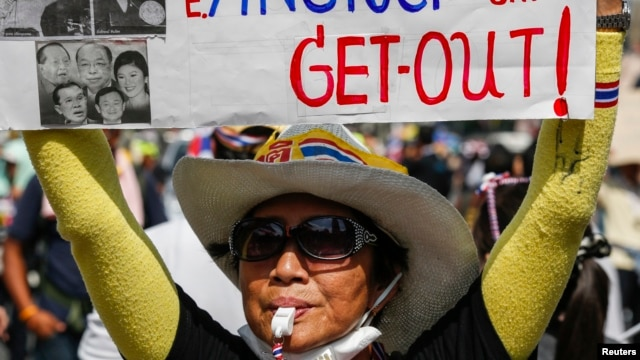 An anti-government protester holds a placard as she gathers with others during a rally at a major business district in Bangkok, Dec. 19, 2013.