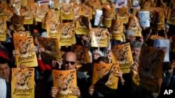 """示威者在巴塞罗那举行集会抗议法官批捕前加泰罗尼亚政府官员。示威者举着加泰罗尼亚语标语""""给政治犯自由""""。(2017年11月5日)"""