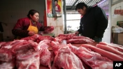 A customer, right, looks at meat at a shop in Shanghai, China, Jan. 17, 2012.