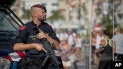 Un policía armado hace guardia donde un terrorista fue baleado por la policía en Cambrils, España, el viernes, 18 de agosto de 2017.