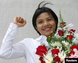FILE - Thai media activist Supinya Klangnarong celebrates at the criminal court in Bangkok, March 15, 2006.