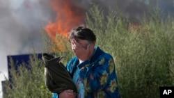 Người phụ nữ khóc gần nơi căn nhà đang bốc cháy của bà ở thành phố Slovyansk, trong vùng Donetsk, miền đông Ukraine 30/6/14