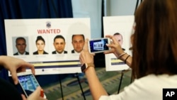 FILE - Reporters photograph wanted posters of people facing criminal charges before a news conference in Washington, June 15, 2017, about the May 16, 2017, altercation outside the Turkish Embassy in Washington during the visit of the Turkish president.