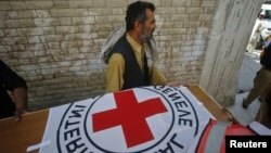Hospital staff and rescue workers carry the casket of Khalil Rasjed Dale, a British doctor working with the the Red Cross, to an ambulance at a hospital in Quetta, April 30, 2012.
