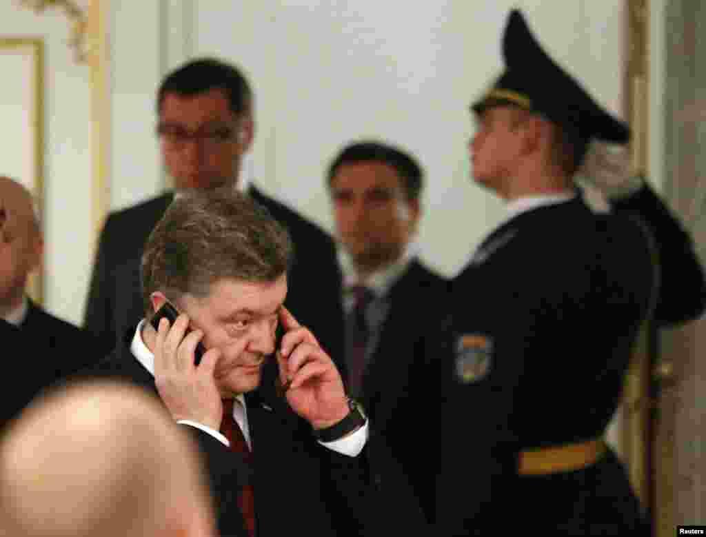 رئيس جمهوری اوکراين، پترو پوروشنکو (جلو) در بيرون اتاق مذاکرات صلح مينسک مشغول گفتگوی تلفنی است – ۲۳ بهمن ۱۳۹۳ (۱۲ فوريه ۲۰۱۵)