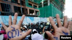 """A man, with his hands painted with words that translate to """"Release"""", demonstrate to demand the release of five opposition members of parliament, as police officers block a street near the Phnom Penh Municipal Court in central Phnom Penh, Cambodia, July 1"""