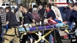 8일 총기난사 사건이 발생한 미국 애리조나 투산의 쇼핑센터 밖에서 응급 구조대원들이 들것을 이용해 희생자를 옮기고 있다.