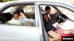 一名妇女开着车和她的两个孩子等着入住无家可归者庇护所。车里是他们的行李。