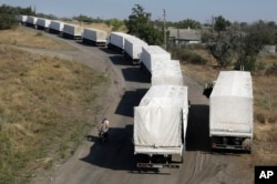 Trucks from Russian aid convoy to Ukraine stand in line as they return to Russia on the border post at Izvaryne, eastern Ukraine, Aug. 23, 2014.