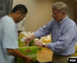Relawan dari gereja membantu membagikan minyak dan beras bagi warga yang datang untuk bahan pangan gratis.