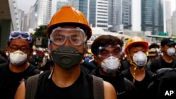 Protesters wearing protection gears march toward the Legislative Council as they continue to protest against the extradition bill in Hong Kong, Monday, June 17, 2019. (AP Photo/Vincent Yu)