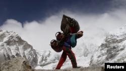 Un nepalés camina con el fondo del Himalaya. Al menos nueve personas murieron en una avalancha cerca de la cima del Monte Manaslu, en Nepal.