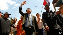 Cambodia's main opposition Cambodia National Rescue Party Vice President Kem Sokha, center, waves during a protest rally in Phnom Penh, Cambodia, May 20, 2013.