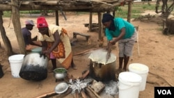 A family in Chachacha village in Chipinge prepares Zimbabwe's popular, thick porridge called sadza made of corn meal and served with relish, March 2016. Most households eat sadza twice a day, at lunch and dinner. But as the country's hunger worsens, the staple food might soon become a delicacy. (S. Mhofu/VOA)