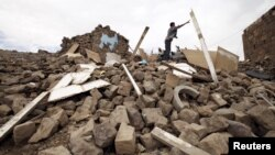 A youth throws a plank of wood away from a pile of rubble of a house destroyed during an airstrike carried out by the Saudi-led coalition in Faj Attan village, Sanaa, Yemen, May 7, 2015.