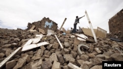 A youth throws a plank of wood away from a pile of rubble of a house destroyed during an air strike carried out by the Saudi-led coalition in Faj Attan village, Sanaa, Yemen, May 7, 2015.