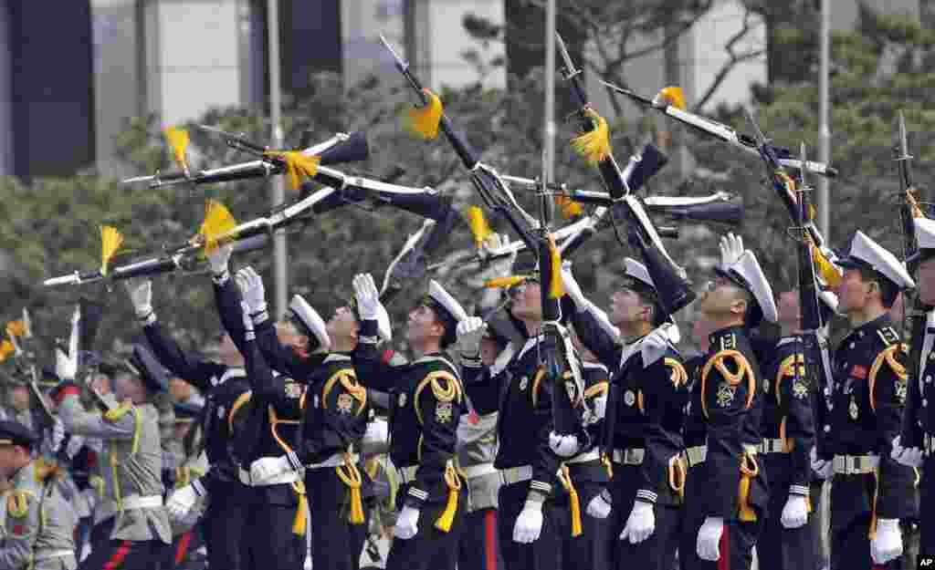 Members of a South Korean honor guard throw their rifles in the air during a weekly demonstration at the War Memorial of Korea in Seoul.