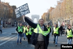 "FILE - A man wearing a yellow vest, a symbol of French drivers' protest against higher fuel prices, holds a placard with the message, ""World Champions in Taxes"", as demonstrators gather on the Champs Elysees in Paris, France, Nov. 17, 2018."