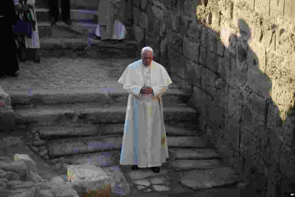 Pope Francis prays as he visits the Bethany beyond the Jordan, which many believe is the traditional site of Jesus' baptism, in South Shuna, Jordan, May 24, 2014.