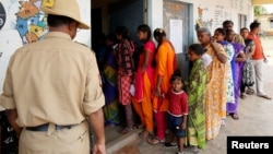 A policeman stands guard as voters wait to cast their ballot outside a polling station during Karnataka assembly elections at a village on the outskirts of Bengaluru, India, May 12, 2018.