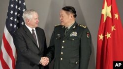 Defense Secretary Robert Gates, left, and China's Minister of Defense Liang Guanglie shake hands before a meeting in Hanoi, Vietnam, 11 Oct. 2010