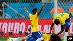 Brazil players celebrate after scoring a third goal during the group A World Cup soccer match against Croatia in the opening game of the tournament at Itaquerao Stadium in Sao Paulo, Brazil, June 12, 2014.