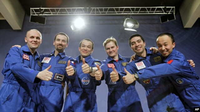 Participants of the Mars500 experiment, which simulated a 520-day flight to Mars, pose for a picture during a news conference in Moscow, November 8, 2011