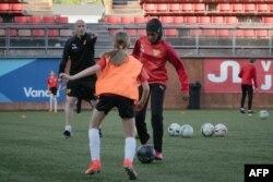 Kamila Nuh (kanan), mengenakan hijab olah raga, saat berlatih sepak bola di Stadion MUP, Vantaa, Finlandia, 1 Juni 2021. (AFP)
