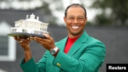 FILE - Tiger Woods wears his green jacket and holds his trophy after winning the 2019 Masters in Augusta, Georgia, April 14, 2019.