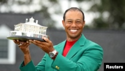 Tiger Woods of the U.S. celebrates with with his green jacket and trophy after winning the 2019 Masters. He was injured in a car accident on February 23, 2021. (REUTERS/Lucy Nicholson)