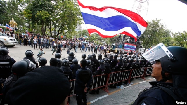 An anti-government protester waves a national flag in front of riot police officers and soldiers guarding the entrance of the National Broadcast Services of Thailand (NBT) television station in Bangkok, May 9, 2014.