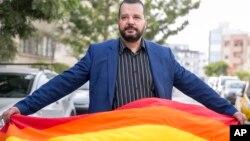 Aktivis LGBT Tunisia, Mounir Baatour, memegang bendera pelangi setelah mendaftarkan pencalonannya sebagai capres dalam pilpres di Tunis, Tunisia, 8 Agustus 2019. (Foto: AP)