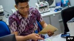 Seorang petugas bank sedang mempersiapkan uang tunai untuk para nasabah yang mendatangi tempat-tempat penukaran uang menjelang liburan Idul Fitri lalu, di Jakarta, 25 Mei 2018.