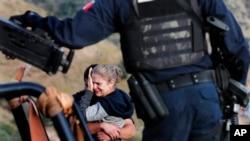 Rodeados de policías mexicanos fuertemente armados, miembros de la familia LeBarón, lloran a sus familiares muertos en una emboscada supuestamente realizada por narcotraficantes en Sonora, México, en octubre pasado. Foto AP