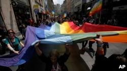 Arhiva - Učesnici Parade ponosa u Beogradu nose veliku zastavu duginih boja, simbol gej pokreta, 27. juna 2013. godine.