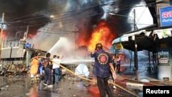 Nhân viên cứu hộ dập tắt đám cháy tại hiện trường vụ nổ bom ở Yala, miền nam Thái Lan.