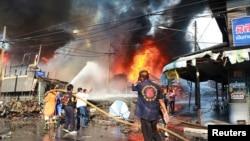 Petugas berusaha memadamkan kebakaran setelah serangan bom di provinsi Yala, Thailand selatan (6/4).
