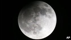 File--The moon seen from the Belarusian capital Minsk, during a partial lunar eclipse, lat April 25, 2013. Scientists believe the Moon and Earth share the same source of water.