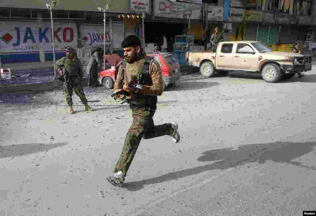 Afghan security forces run in the aftermath of a suicide car bomb attack in Jalalabad province, Afghanistan, March 20, 2014.