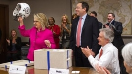 Secretary of State Hillary Rodham Clinton holding up a football helmet presented to her as she returned to work after a month-long absence caused first by a stomach virus, then a fall and a concussion, and finally a brief hospitalization for a blot clot n