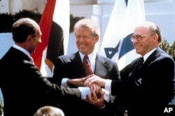 FILE - In this March 26, 1979 file photo, Egyptian President Anwar Sadat, left, U.S. President Jimmy Carter, center, and Israeli Prime Minister Menachem Begin clasp hands on the North Lawn of the White House as they completed signing of the peace treaty b